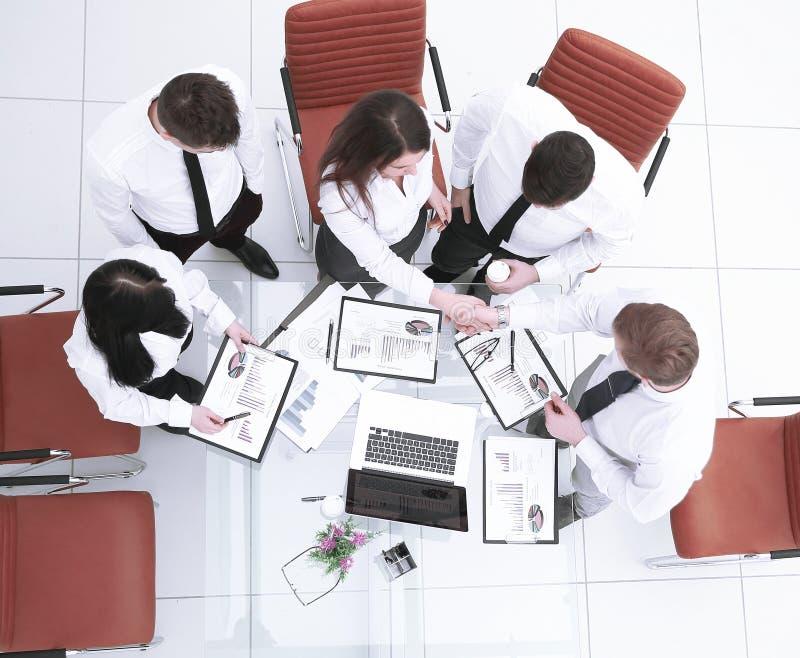 Visión superior colegas que sacuden las manos antes de una reunión de funcionamiento en la oficina imagen de archivo libre de regalías