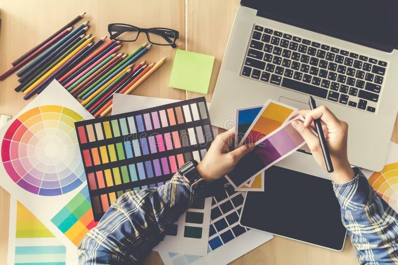 Visión superior Diseñador en la camisa escocesa, funcionamiento creativo gráfico en la pluma del ratón, ordenador portátil en ofi imagen de archivo libre de regalías