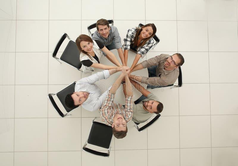 Visión superior el equipo sonriente del negocio dobló sus manos juntas fotografía de archivo libre de regalías