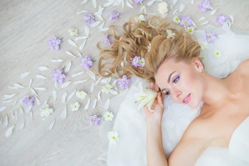 VISIÓN SUPERIOR: El retrato de la muchacha bastante rubia en un piso con un campo florece fotografía de archivo