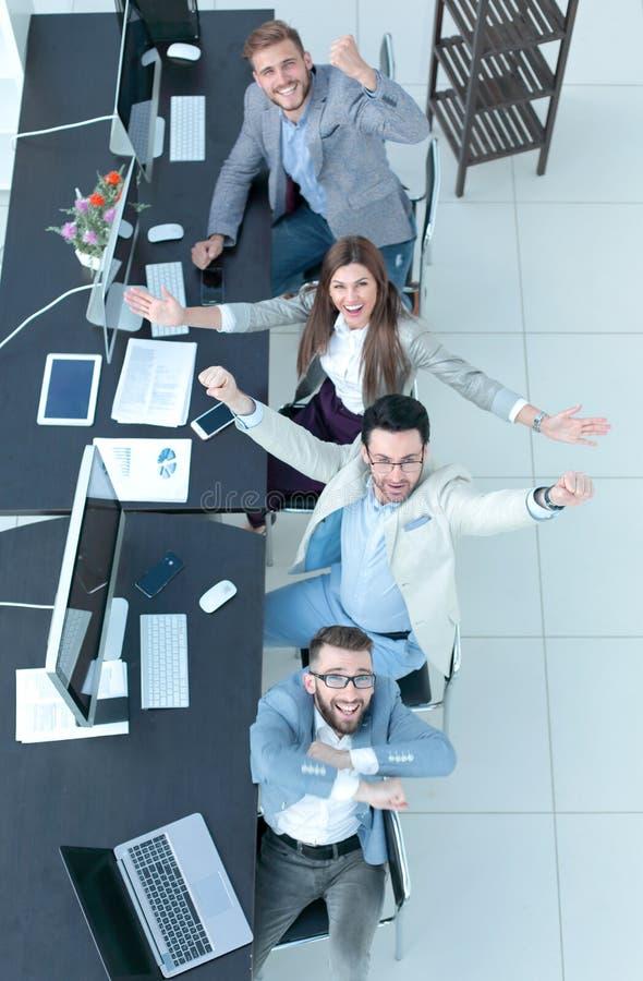 Visión superior equipo feliz del negocio que se sienta en el escritorio foto de archivo