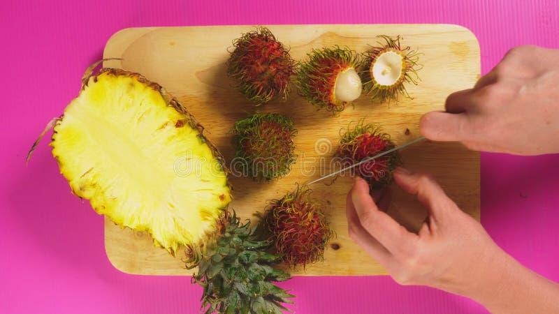 Visión superior, frutas femeninas de los cortes de la mano con un cuchillo en un tablero de madera, piña y rambutan El concepto d fotos de archivo