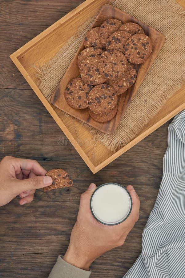 Visión superior - galletas de microprocesador de chocolate en la placa y la mano que sostienen el vidrio de leche en una tabla de fotos de archivo