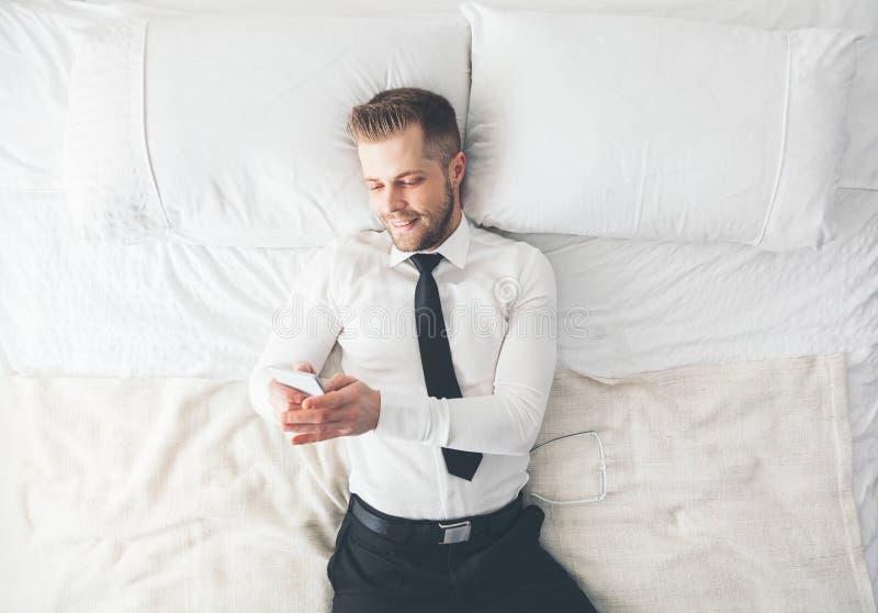 Visión superior Hombre de negocios hermoso que miente en la cama que manda un SMS de su smartphone fotografía de archivo libre de regalías