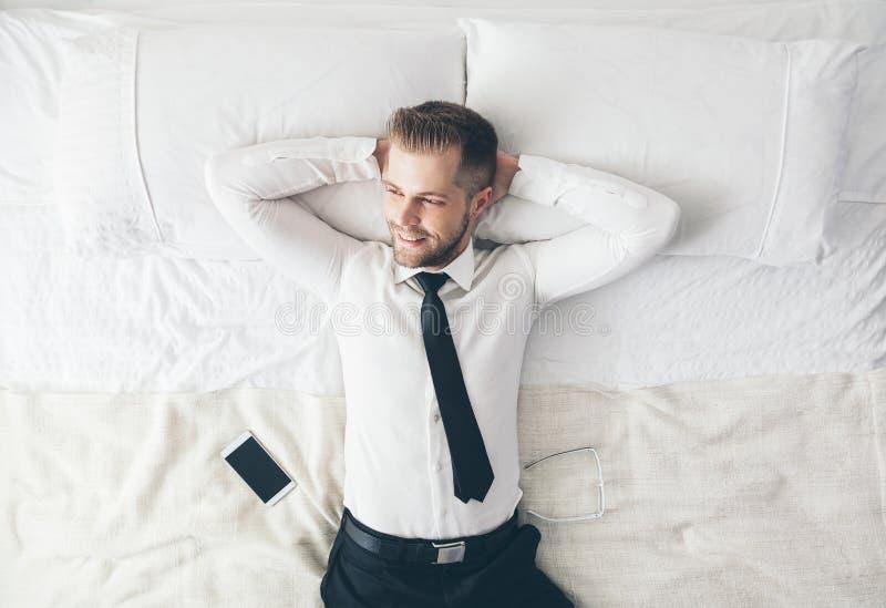 Visión superior Hombre de negocios hermoso que se relaja en cama después de un día duro en el trabajo imagen de archivo