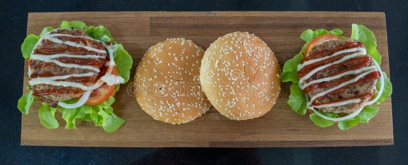 Visión superior, ingredientes de las hamburguesas colocadas en una tabla de cortar de madera imagen de archivo