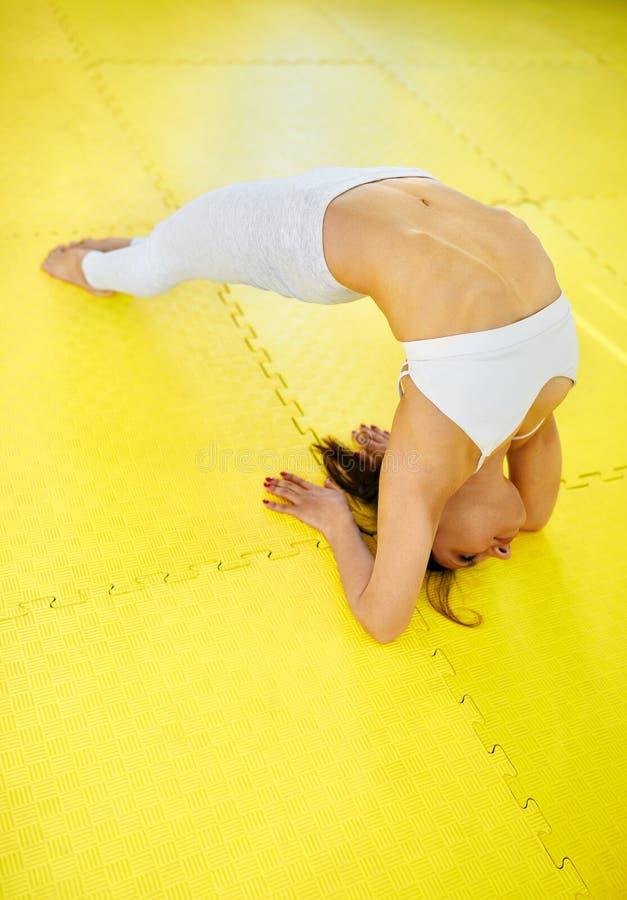 Visión superior - mujer deportiva joven hermosa en yoga practicante de la ropa de deportes blanca en la estera amarilla en un gim foto de archivo