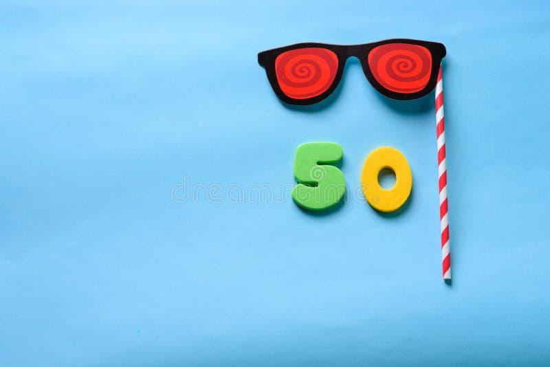 Visi?n superior puesta plana n?mero 50 y m?scara de papel linda del carnaval de las gafas de sol fotos de archivo