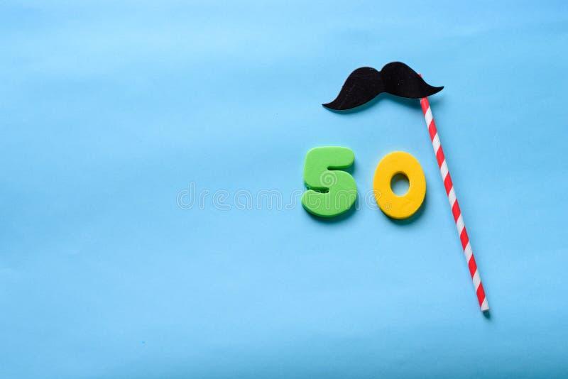 Visi?n superior puesta plano n?mero 50 y bigote lindo de la m?scara de papel del carnaval fotografía de archivo