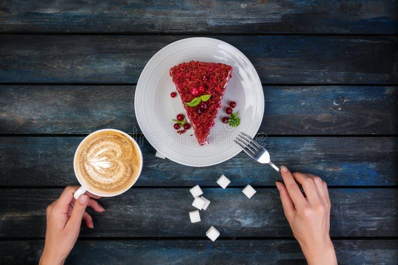 Visión superior Rebanada de torta del terciopelo y de café rojos deliciosos del latte con las manos del ` s de las mujeres y el a fotografía de archivo libre de regalías