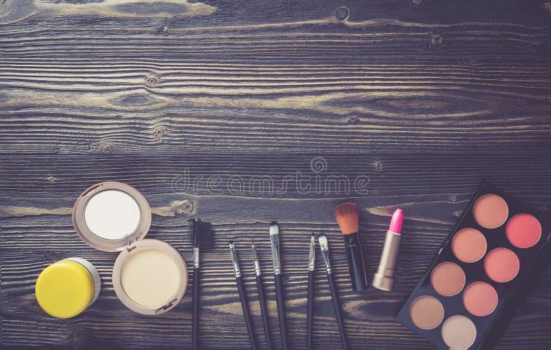 Visión superior una colección de maquillaje cosmético en el fondo de madera de la tabla, concepto cosmético de la moda de los pro imagenes de archivo