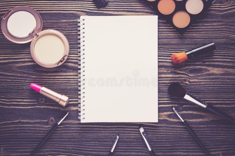 Visión superior una colección de maquillaje cosmético y de cuaderno en fondo de madera de la tabla imagenes de archivo