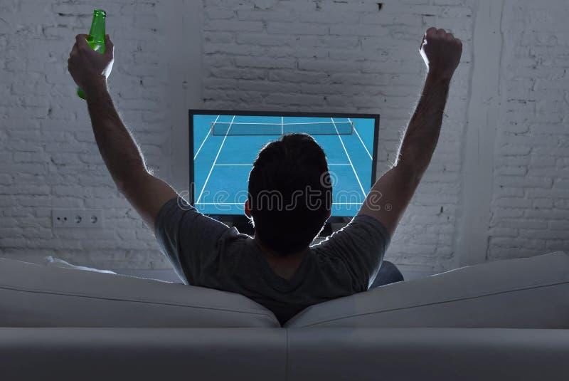 Visión trasera con el partido de observación solo del tenis del Grand Slam del hogar del hombre joven en la televisión en el sofá fotografía de archivo libre de regalías