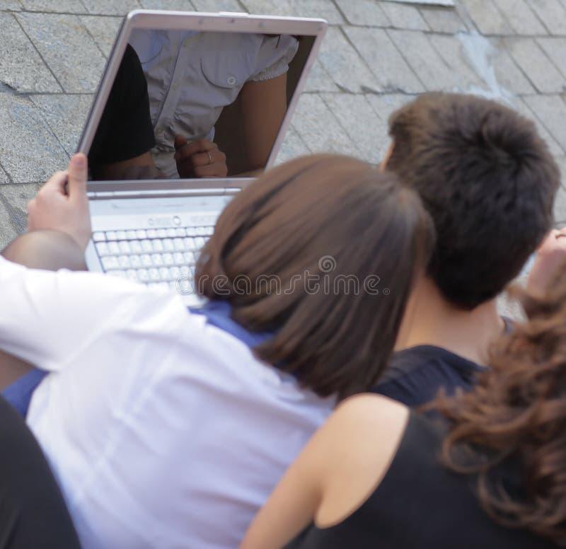 Visión trasera el grupo de amigos de estudiantes con un ordenador portátil foto de archivo