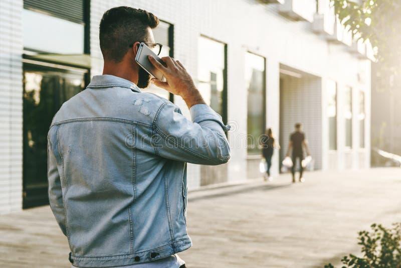 Visión trasera Hombre de negocios del inconformista con la barba, en chaqueta del dril de algodón y paseos de moda de los vidrios imágenes de archivo libres de regalías