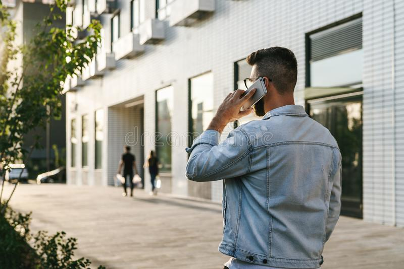 Visión trasera Hombre de negocios del inconformista con la barba, en chaqueta del dril de algodón y paseos de moda de los vidrios fotografía de archivo
