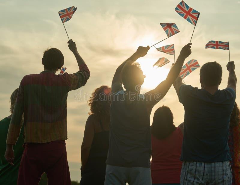 Visión trasera, silueta del pueblo británico con las banderas imagenes de archivo