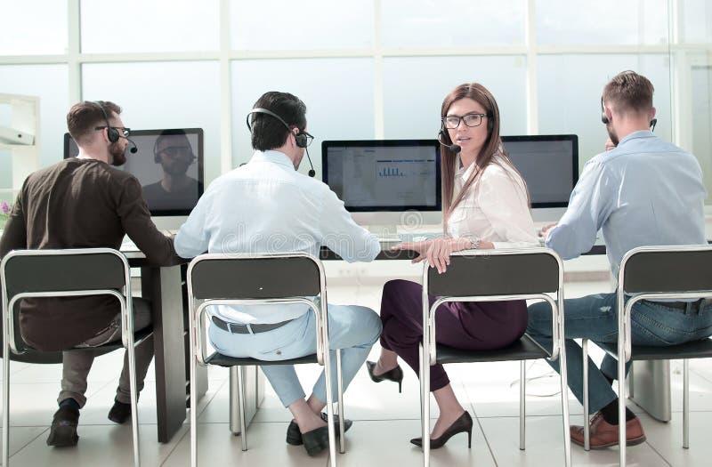 Visión trasera un grupo de personas en los trabajos de las auriculares en la oficina del centro de negocios fotografía de archivo