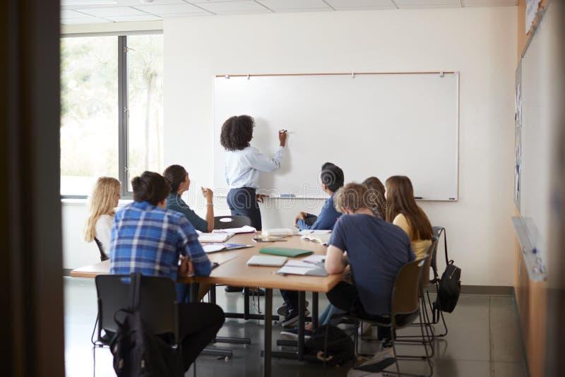 Visión a través de la entrada de la clase de la matemáticas de At Whiteboard Teaching del profesor particular de la High School s imagen de archivo