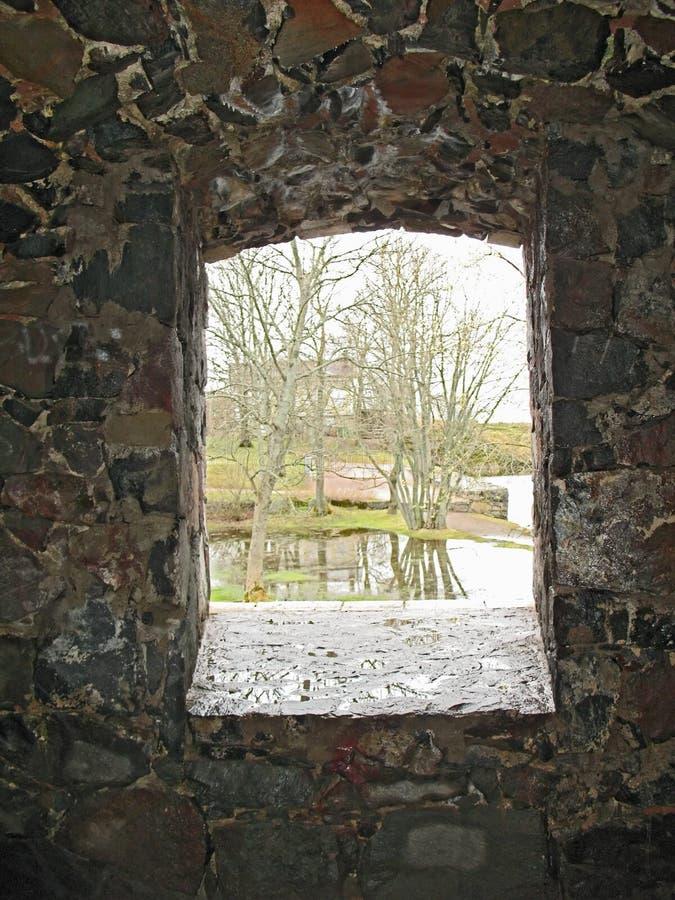 Visión a través de la ventana de piedra en la pared del castillo. imagen de archivo libre de regalías