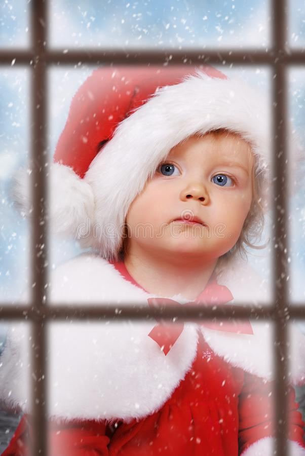 Visión a través de la ventana en bebé lindo en el sombrero de santa foto de archivo