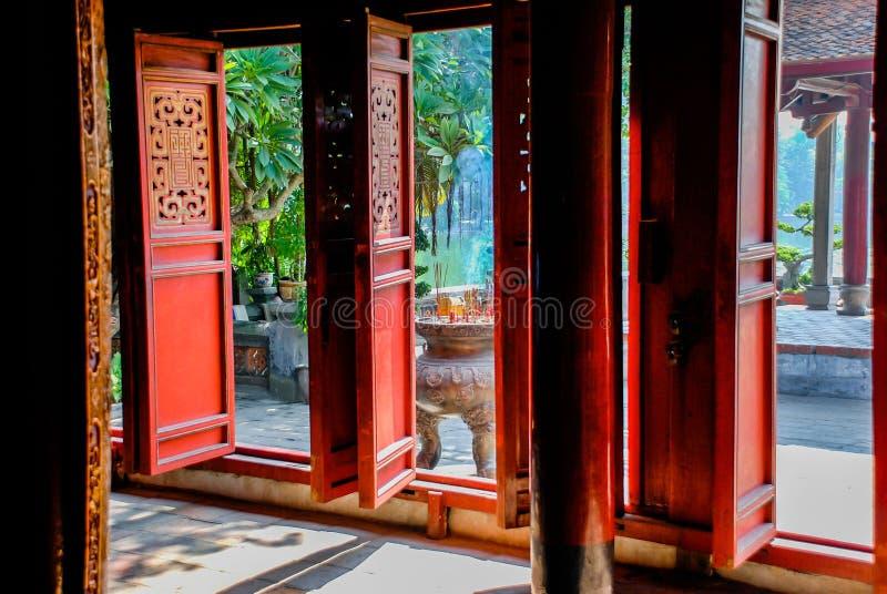 Visión a través de las puertas de madera rojas del templo de la literatura en Hanoi imagenes de archivo
