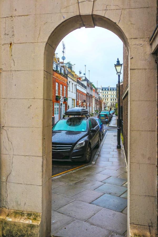 Visión a través de un arco de piedra de una calle de Londres a una calle lateral estrecha alineada por las casas de fila y los co fotos de archivo libres de regalías