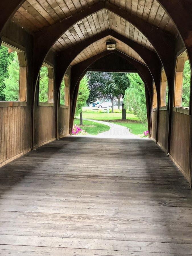 Visión a través de un puente cubierto de madera marrón en parque de la ciudad foto de archivo