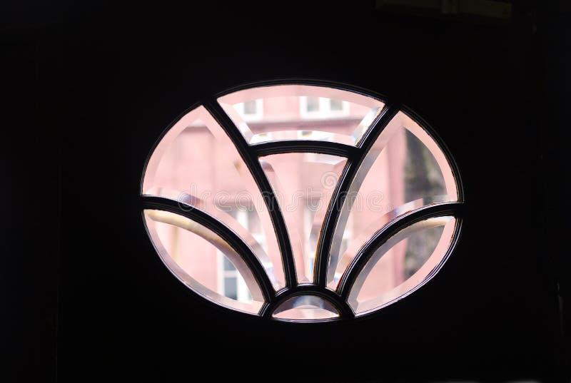 Visión a través de una ventana oval en una puerta vieja de la casa a un hous rosado fotografía de archivo