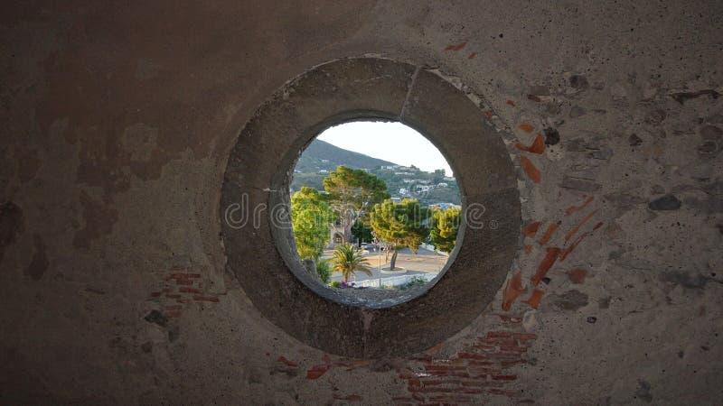 Visión a través de una ventana redonda en una pared de piedra fotos de archivo libres de regalías