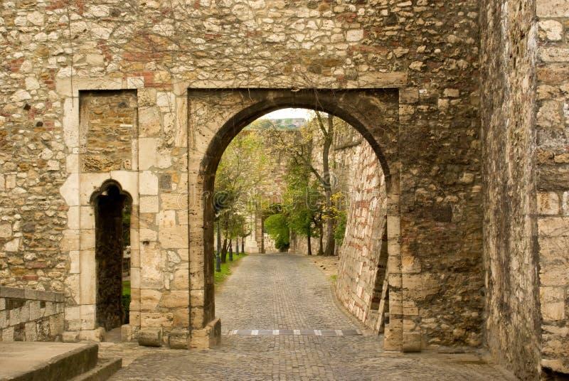 Visión a través del arco de piedra viejo en el pavimento imagenes de archivo