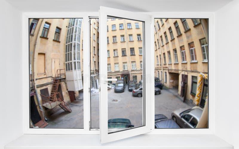 Visión a través del marco de ventana del pvc en la primera planta en el cuadrilátero estrecho con los coches parqueados fotos de archivo libres de regalías