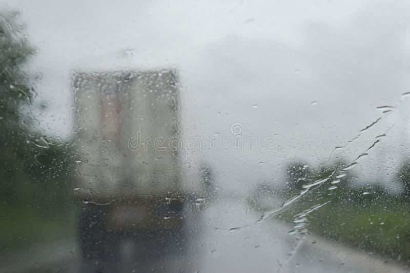 Visión a través del parabrisas en el camino en la estación de lluvias foto de archivo