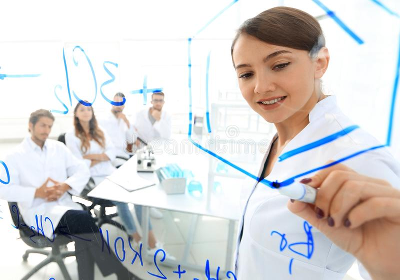 Visión a través del tablero transparente bioquímico de sexo femenino que analiza la información imagenes de archivo