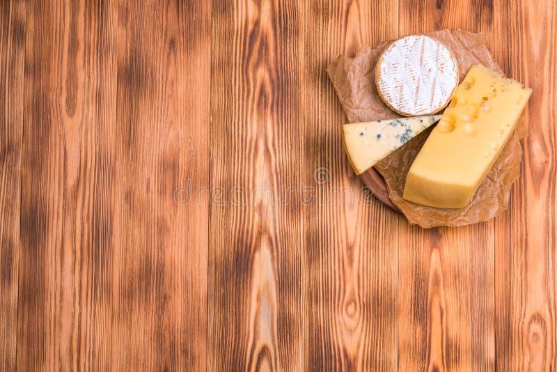 Visi?n desde la tapa pedazos de diverso queso en una tabla de madera Copie el espacio foto de archivo