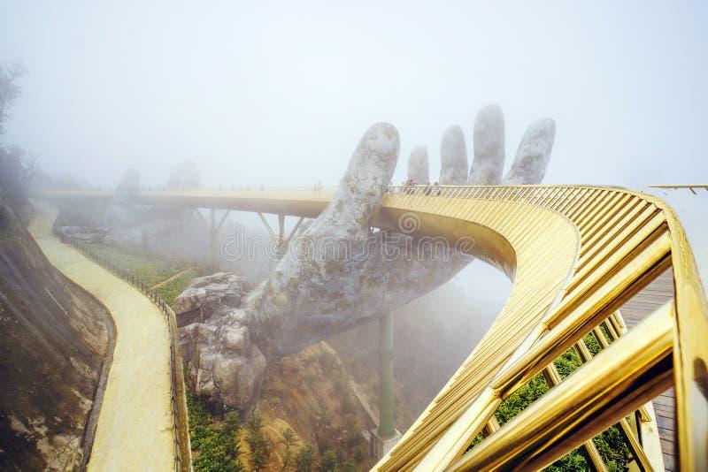 Visi?n en la niebla del puente de oro en las colinas del Na de los vagos en Da Nang en d?a lluvioso foto de archivo