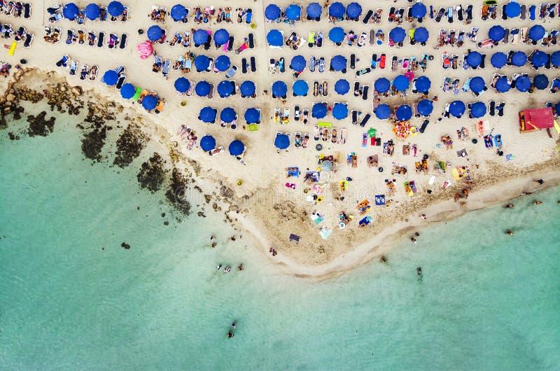 Visi?n a?rea que sorprende desde arriba sobre la playa de Nissi en Chipre Playa de Nissi en la alta marea Los turistas se relajan fotos de archivo libres de regalías