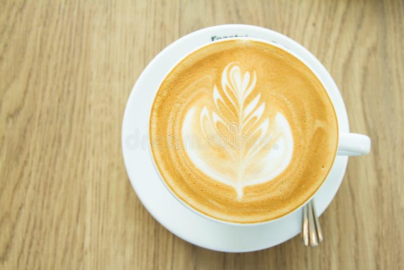 Visi?n superior Arte caliente del latte de la taza de café en la tabla de madera en el café imágenes de archivo libres de regalías