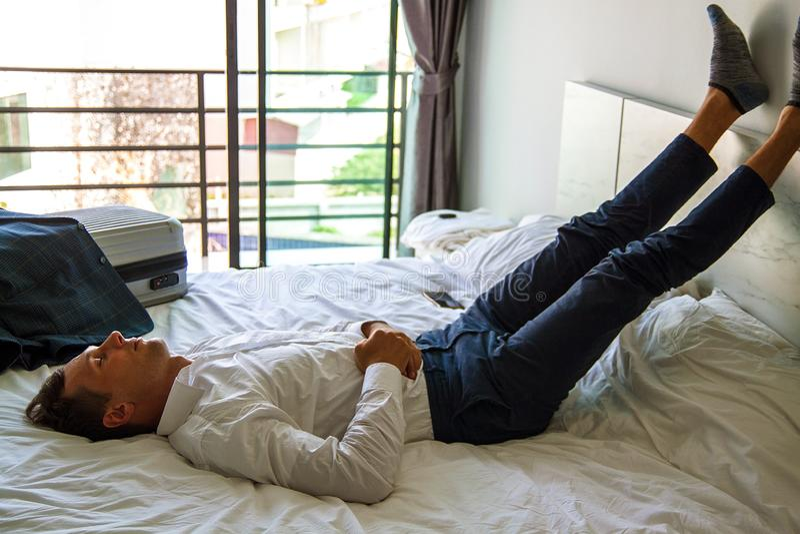 Visi?n superior Hombre de negocios joven que se relaja en cama despu?s de un d?a duro en el trabajo foto de archivo libre de regalías