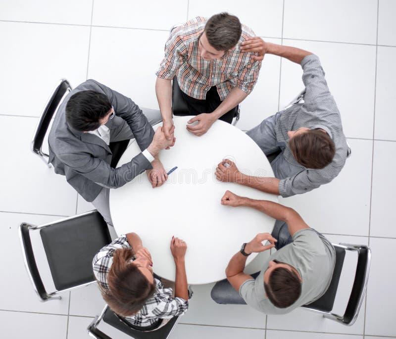 Visi?n superior unidad de negocio creativa que se sienta en la mesa redonda imagen de archivo
