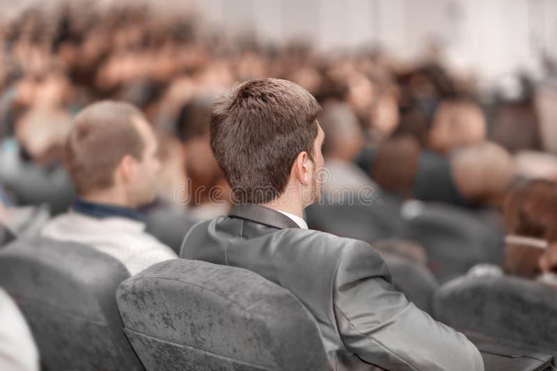 Visi?n trasera los hombres de negocios escuchan la conferencia en la sala de conferencias imagen de archivo