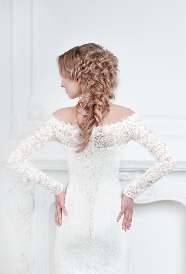 Visi?n trasera novia en la situación del vestido de boda delante del espejo foto de archivo libre de regalías