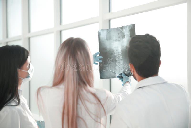 Visi?n trasera un grupo de cirujanos que discuten la radiograf?a imagenes de archivo