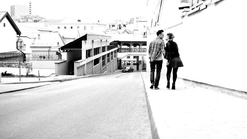 Visi?n trasera un par en el amor que camina en la acera en una ciudad moderna fotos de archivo
