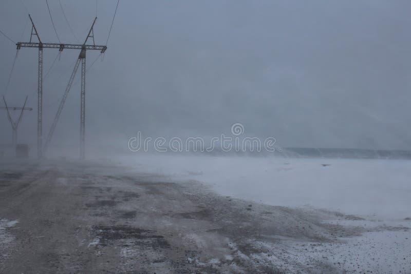 A visibilidade pobre alta elétrica na estrada no inverno na tempestade de neve da trilha varre condições meteorológicas perigosas fotos de stock royalty free