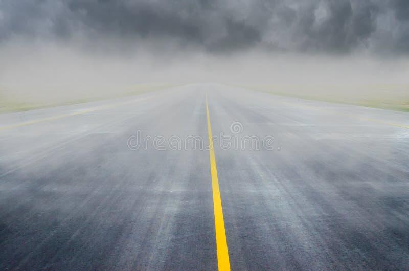 Visibilità difficile dovuta annebbiare sulla pista di rullaggio della pista dell'aeroporto, la pista della direzione immagini stock
