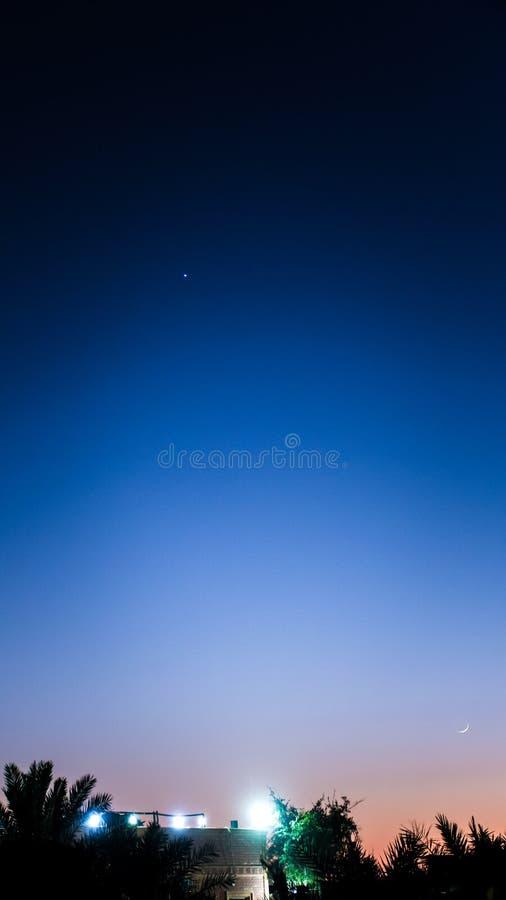 Visible Venus and crescent Moon at dusk near farm house stock photography