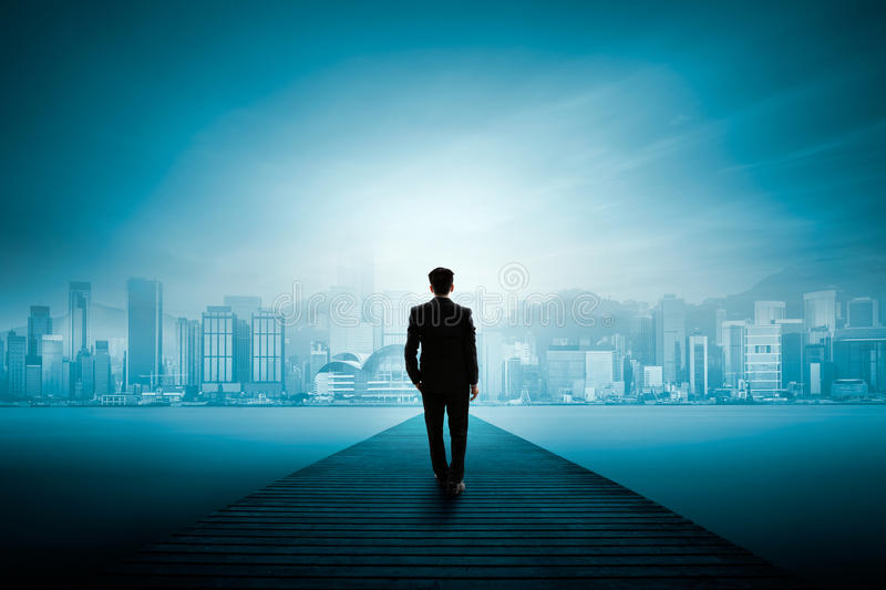 Vision. Busness man standing on wooden bridge and looks at the city stock image