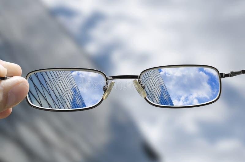 Vision d'un bâtiment en verre d'affaires par des verres photographie stock libre de droits