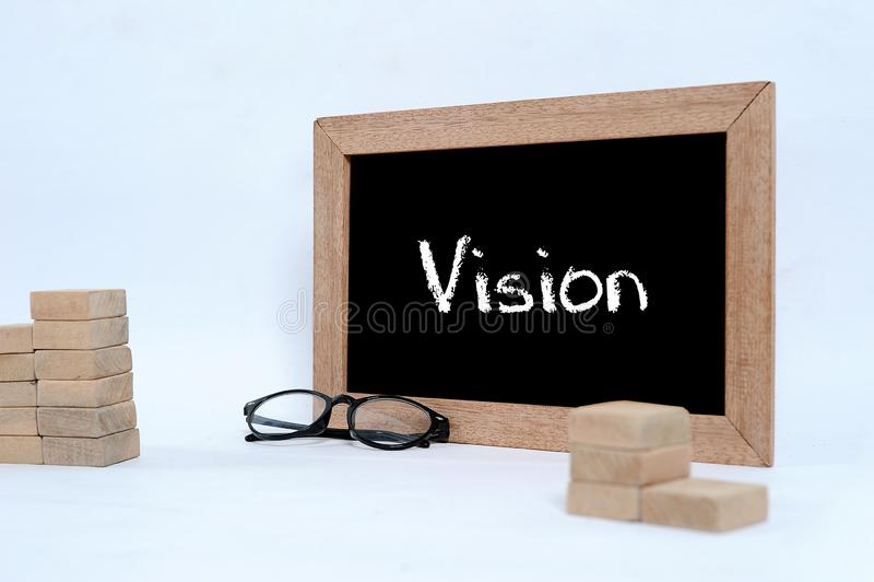 Vision en la pizarra con la escritura de la tiza Bloque del vidrio del ojo y madera que apila como s?mbolo de la escalera del pas fotografía de archivo